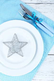 Witte borden, vork, mes en kerstversiering op blauwe polka dot servet op houten ondergrond