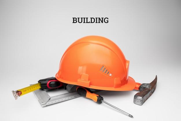 Witte bouwhelm, meetlint, hamer, schroevendraaier. inscriptie constructie. conceptenarchitectuur, bouw, techniek, ontwerp, reparatie.