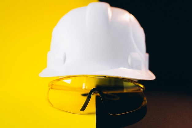 Witte bouwvakker met geïsoleerde beschermingsoogglazen