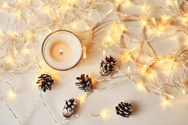 Witte brandende kaars, dennenappels en slinger lichten, bovenaanzicht. gezellig huis en hygge concept