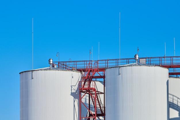 Witte brandstofopslagtanks tegen blauwe hemelachtergrond
