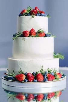 Witte bruidstaart met fruit, aardbei en bosbessen