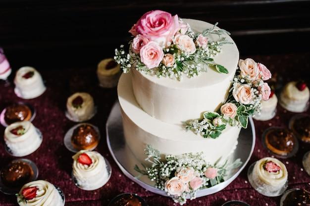 Witte bruidstaart met roze bloemen en groenen op een feestelijke tafel