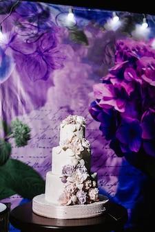 Witte bruidstaart met roze bloemen op een feestelijke tafel met gebak. close-up van taart. zoete tafel.