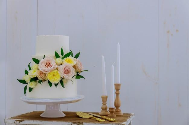 Witte bruidstaart met verse bloemen en kaarsen op witte achtergrond.