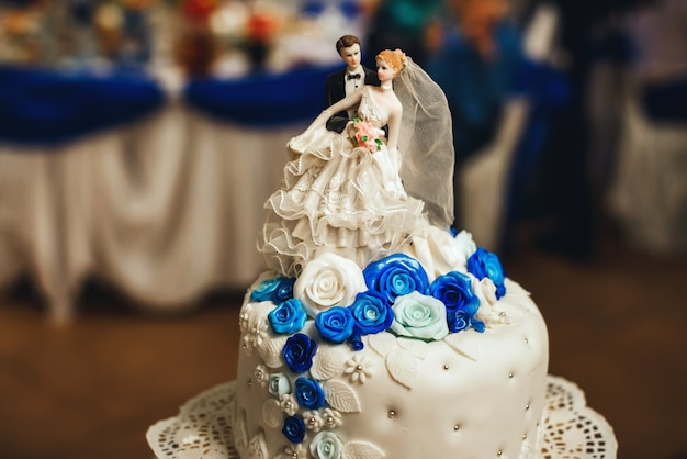 Witte bruidstaart versierd met blauwe rozen met rijen en een figuur van de bruid en bruidegom