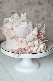 Witte bruidstaart versierd met verse rozen, pioenrozen en groen