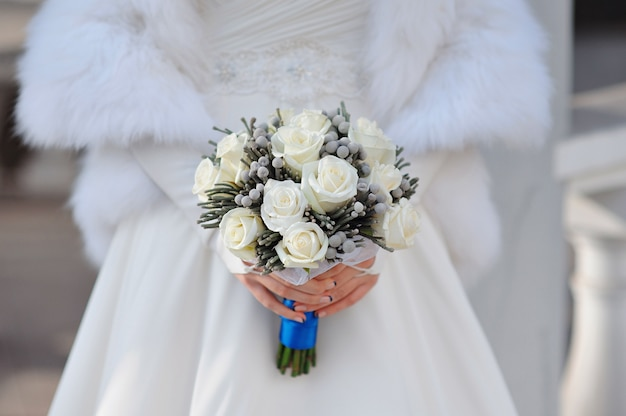 Witte bruiloft boeket rozen in handen van de bruid