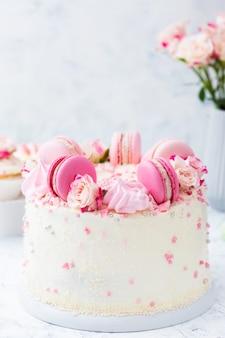 Witte bruiloftstaart met macarons en rozen