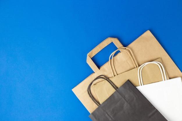 Witte, bruine en zwarte papieren zakken met handvatten op blauwe achtergrond. platte banner, bovenaanzicht, kopieerruimte, afvalvrij, plasticvrije artikelen. mockup eco-pakket, levering of online winkelconcept