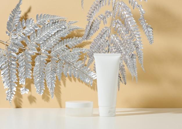 Witte buis voor cosmetica, een pot room en bladzilver op een witte tafel. cosmetisch op een beige schaduwachtergrond. crèmefles, lotion, reinigingsmiddel, shampoo voor huidverzorging