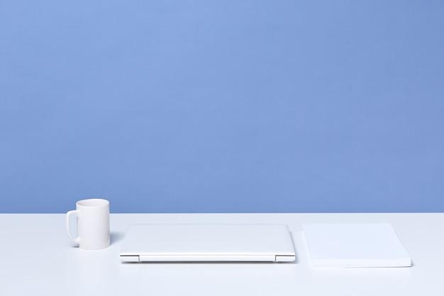 Witte bureau met gesloten laptop en koffie of thee kopje, stapel papier