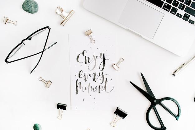 Witte bureau-werkruimte met quote enjoy every moment en kantoorbenodigdheden