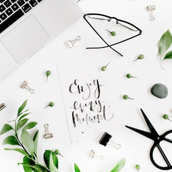 Witte bureau-werkruimte met quote enjoy every moment, groene bladeren en kantoorbenodigdheden