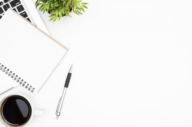 Witte bureaulijst met leeg notitieboekje, laptop computer, kop van koffie en levering. bovenaanzicht, plat leggen.