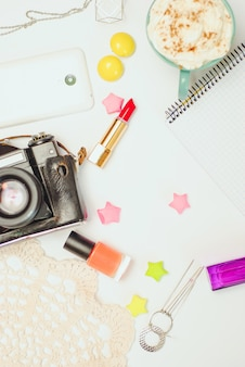 Witte bureaulijst met smartphone, uitstekende camera, koffie en schoonheidsmiddelen.