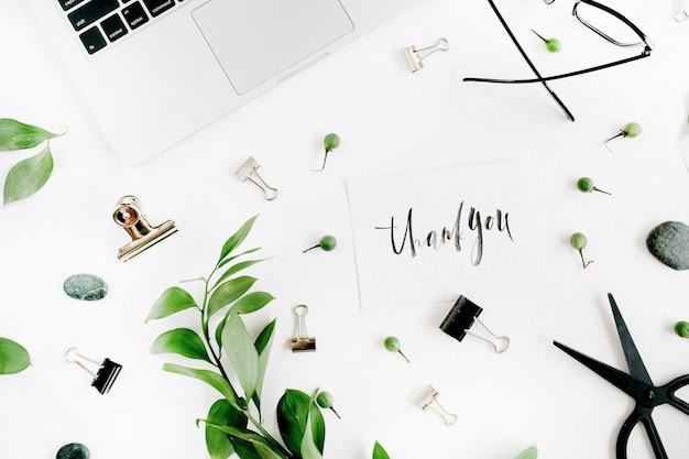 Witte bureauwerkruimte met citaat dank u, groene bladeren en kantoorbenodigdheden