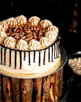 Witte cake gegoten met chocolade en versierd met noten