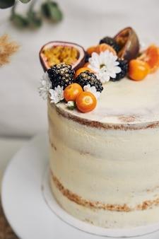 Witte cake met bessen en passievruchten naast een plant erachter op wit