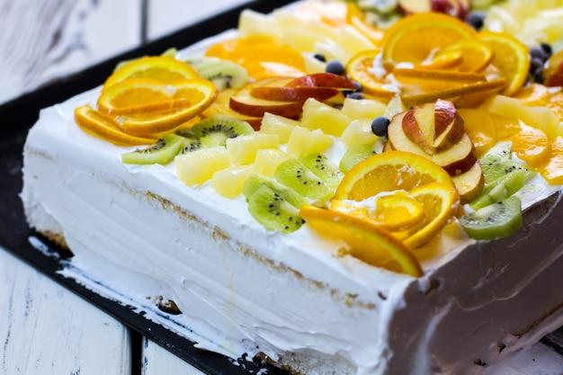 Witte cake met stukjes fruit. plakken van kiwi en sinaasappel. dure op maat gemaakte taart. feestelijk dessert in een restaurant.
