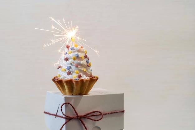 Witte cake met wonderkaarsen op de doos van de levering van wit papier op de achtergrond set sail champagne