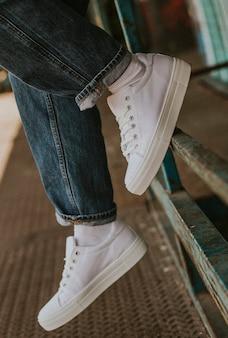 Witte canvas sneakers op jeansmodel