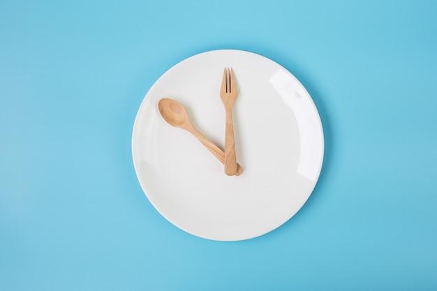 Witte ceramische plaat met mes, lepel en vork op blauwe achtergrond. intermitterend vasten concept