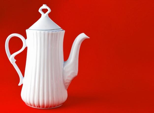 Witte ceramische theepot op rode achtergrond, exemplaarruimte