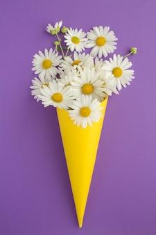 Witte chamomiles in een papieren gele kegel op de violette achtergrond