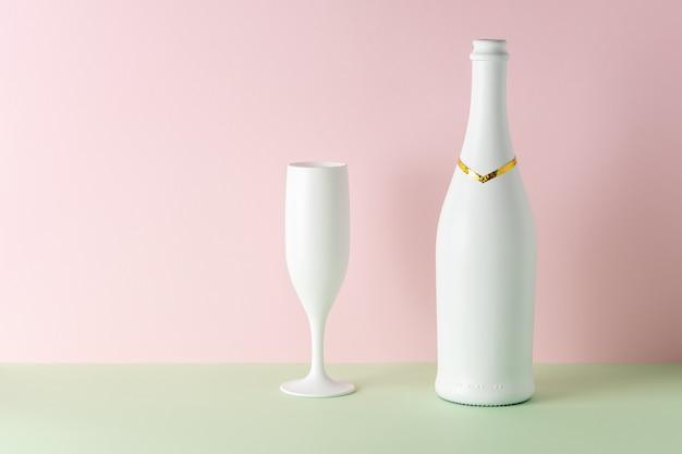 Witte champagnefles en champagneglas op lichte achtergrond.