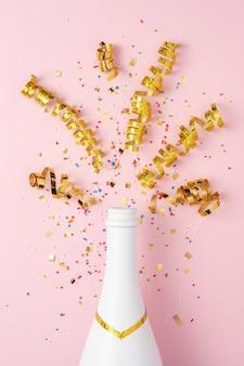 Witte champagnefles met confetti en feestwimpels op roze achtergrond.