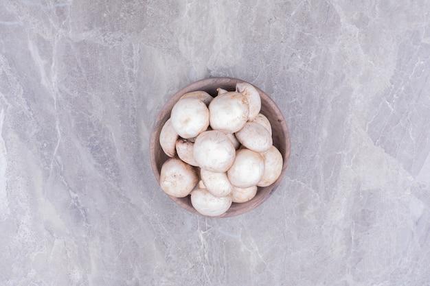Witte champignons in een houten beker, bovenaanzicht