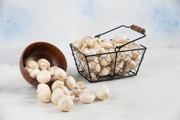 Witte champignons in een houten beker en een metalen mand.