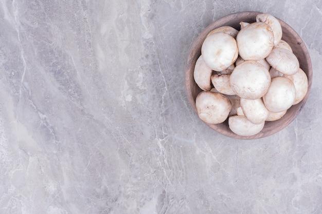 Witte champignons in een houten beker.