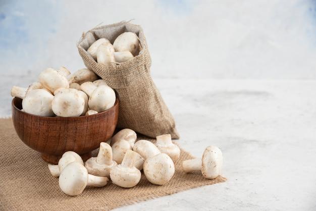 Witte champignons in een houten kopje op een stuk jute.