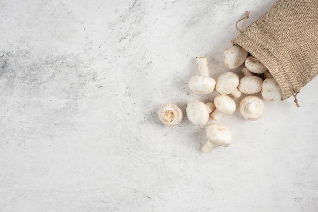 Witte champignons in rustieke manden op marmeren tafel.
