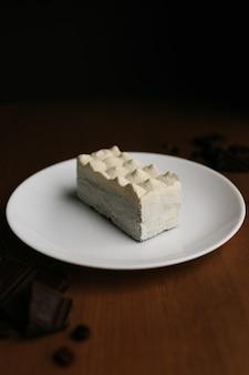 Witte cheesecake op plaat op bruin houten tafel, chocolade.