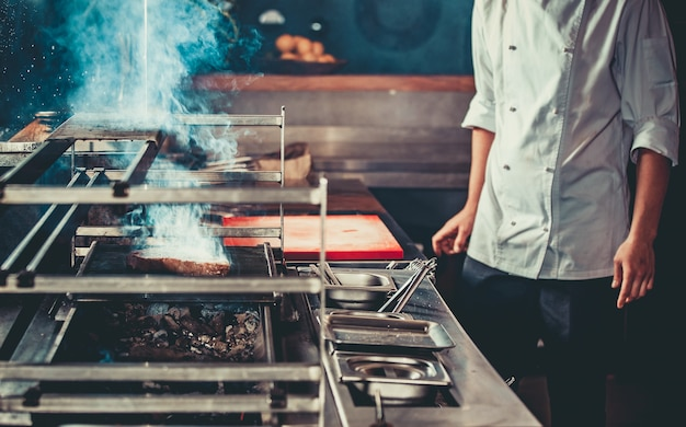 Witte chef-kok in schort die bij de vuurpot staat met kolen, alleen handen. man koken biefstuk in het interieur van de moderne professionele keuken