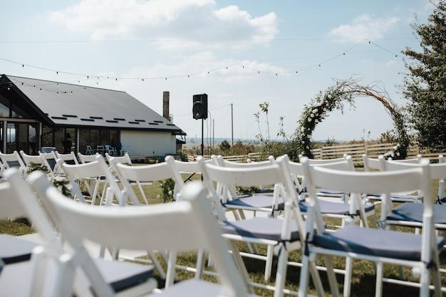 Witte chiavari stoelen voor gasten, ceremoniële huwelijksboog op de versierde voor de huwelijksceremonie