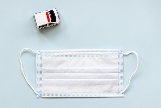 Witte chirurgische mondmasker en speelgoed ambulance auto op blauwe achtergrond. tijdens het coronavirus covid-19 concept. plat leggen