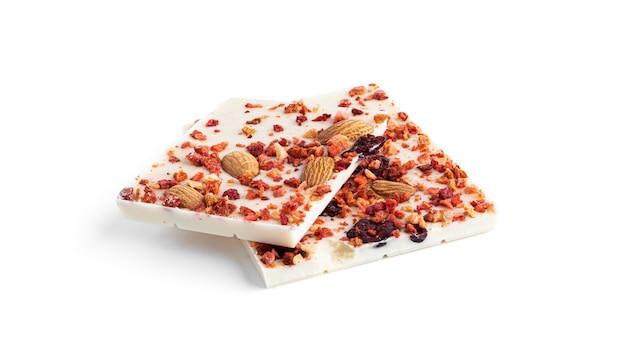 Witte chocolade met amandelen, veenbessen en aardbei plakjes geïsoleerd op een wit oppervlak