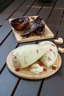 Witte chocolade paasei met gekonfijte aardbeien op een houten plaat. een paasei van pure chocolade met knapperige amandelen