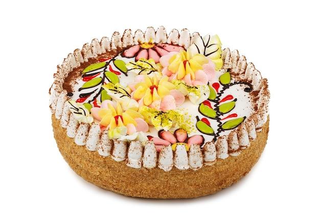 Witte chocoladecake versierd met crèmekleurige bloemen geïsoleerd