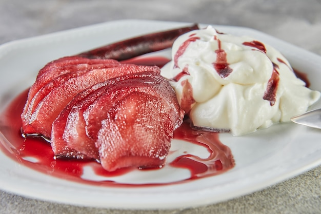 Witte chocolademousse met peren in rode wijn op serveerschaal.