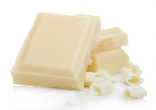Witte chocoladestukken en krullen die op wit worden geïsoleerd.