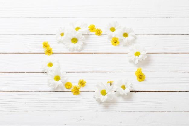 Witte chrysant en geel klein hoefblad op witte houten achtergrond
