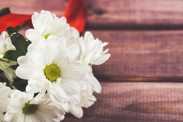 Witte chrysantenbloemen met rood lint op hout