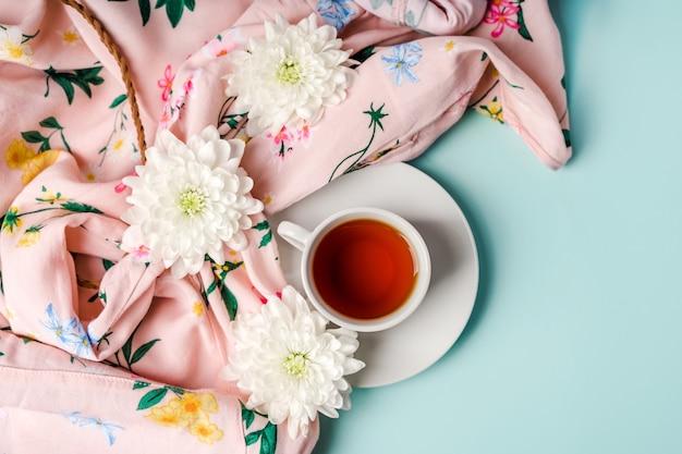 Witte chrysantenbloemen op een damesoverhemd en een mok thee op een lichtblauwe achtergrond