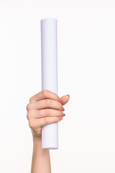 Witte cilinder van de rekwisieten in de vrouwelijke handen op een witte achtergrond met juiste schaduw