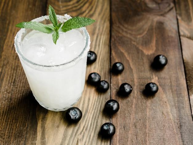 Witte cocktail met ijs naast bosbessen